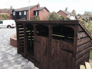 Dark brown log store with bin store